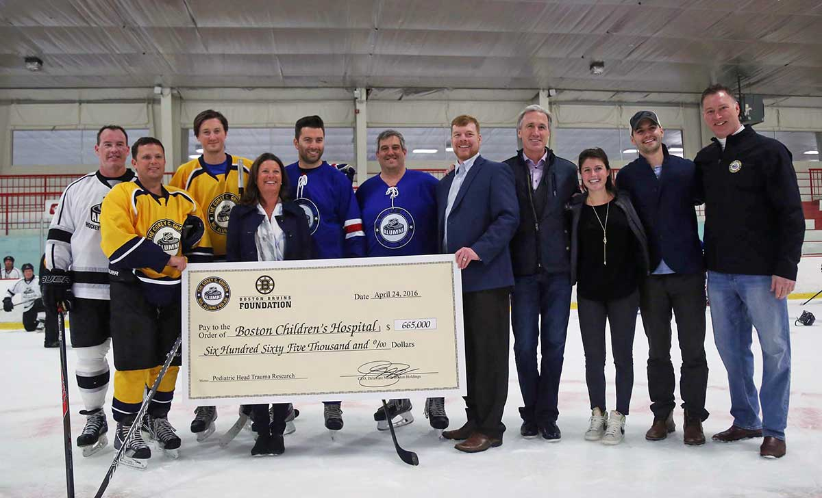 Team Bain Capital captain Jay Corrigan (second from left) with draft pick Ray Bourque (second from right) and NHL Pro-Am founder Mike Griffin (at right)
